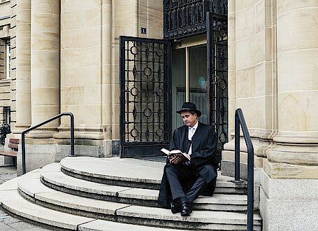 Hartmut Hardt, lawyer, Association of German Engineers (VDI) studying a law book in front of the court building